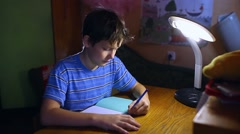 Teenage boy writes in notebook homework sitting at a table lamp evening room Stock Footage