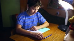 Teenage boy writes in notebook homework sitting at lamp table  evening room Stock Footage