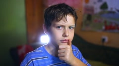 Shaggy tired teenage boy thinking in a room in the evening light - stock footage