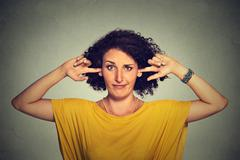 Annoyed upset angry woman plugging her ears with fingers doesn't want to list Stock Photos