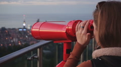 Travel: young woman tourist looking at city through coin-operated binoculars at Stock Footage