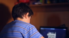 Teenage playing boy computer video game sitting back evening room Stock Footage