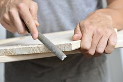 young man filing a wooden board with a rasp - stock photo