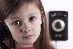 Serious sad child talking on phone, white background - stock photo