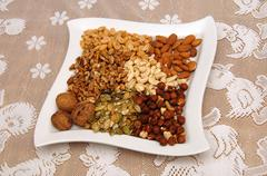 Nuts on a white plate Stock Photos