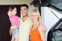 happy family with hatchback car at home parking - stock photo