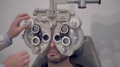 Optician setting a phoropter before a eyesight visit Stock Footage