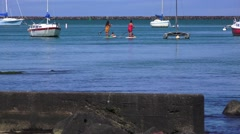 Hawaiian women on paddle boards with children Stock Footage
