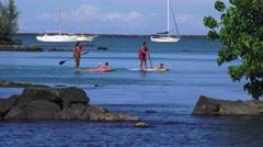Hawaiian women on paddle boards, children riding   ,Hawaii   Stock Footage