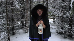 Beautiful girl with a candle lantern is standing in a gloomy winter forest - stock footage