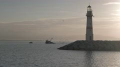 Silhouette of lighthouse with fishing boat escorted by seagulls crossing the sea Stock Footage