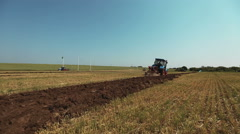 tractor with plow plowing the land  and making furrows - stock footage