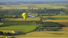 Beautiful wide shot of single hot air balloon against agriculture Stock Footage