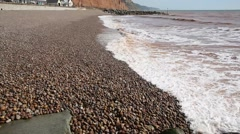 Beach with pebbles and shingle and waves Sidmouth Devon Stock Footage