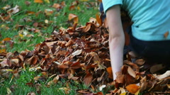 Child Playing and Getting Up Out of Leaf Pile in Slow Motion - stock footage