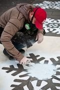 painter artist draws on a sidewalk of bomb snowflakes - stock photo