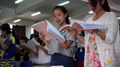 Young students reading textbook in classroom Stock Footage
