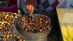 Stock Video Footage of cooking edible chestnuts on a grill in the Asian market