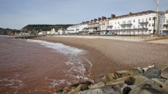 Devon coast town of Sidmouth England UK with pebble beach and waves and hotels Stock Footage