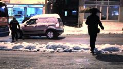 Snow covered winter street at night in light of lamps and automobile headlights - stock footage