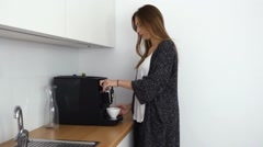 Beautiful girl is making coffee in coffee machine and drinking it. Indoor photo - stock footage