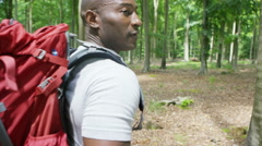 4K Attractive man hiking in the woods beckons to camera to follow him Stock Footage