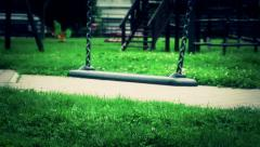 Scary empty swing with chains swaying at playground for child Stock Footage