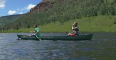4k Guys paddle a canoe in a mountain lake Stock Footage
