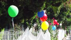 Colorful Balloons Bob in the Wind on White Fence Stock Footage