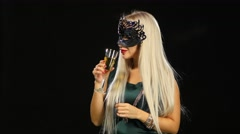 Woman with glass of champagne wearing venetian masquerade mask at party, on Stock Footage