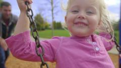 Father pushes happy daughter on swing Stock Footage
