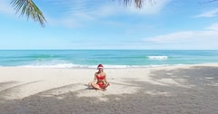 Beautiful Caucasian christmas woman in santa hat and red bikini doing yoga and Stock Footage