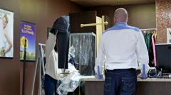 Man taking his pants at dry cleaning store Stock Footage