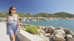 Happy Woman Walking On Footpath By Harbor Wearing Sunglasses on Mallorca, Spain Stock Footage