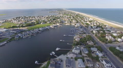 4K aerial over summer beach town with the beach and ocean Stock Footage