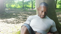 4K Attractive African American man hiking in the woods takes a rest Stock Footage