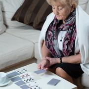 Senior woman playing cards alone Stock Photos