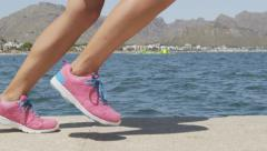 Jogger In Sports Shoes Running On Footpath By Sea - Female Runner Workout - stock footage