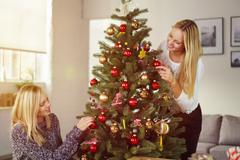 Two pretty girlfriends decorating an Xmas tree Stock Photos