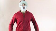 Santa Claus dances with a Christmas wreath - stock footage