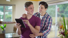 4K Affectionate young gay couple relaxing at home with computer tablet Stock Footage