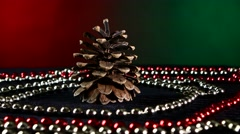 Pine cone for Christmas or New Year and beads, rotation, on red and green Stock Footage