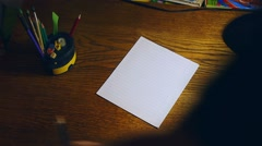 Artist sits down and begins to draw in pencil on a sheet of paper Stock Footage