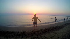 happy man running on the beach against sunset reflection and jumps in the wat - stock footage