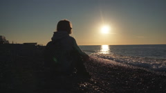 Travel: Silhouette of beautiful girl tourist seating on the beach at sunset Stock Footage