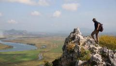 Backpacker climbs to the top of the mountain by autumn morning. Panoramic view. Stock Footage