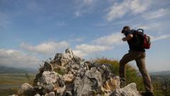 Walking tourists climb to mountain top and lifts his arms up enthusiastically Stock Footage