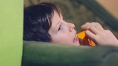 Teenage boy is eating an orange and peel Stock Footage