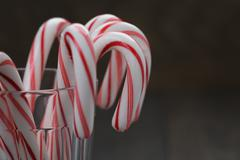 striped candy canes in faceted glass on wood table - stock photo