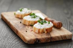 crunchy baguette slices with cream cheese and green onion - stock photo